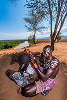 Kara tribe man styling hair, Omo Valley, Ethiopia.