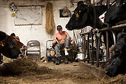 Pete Yetnick, of Stockbridge, changes his boots before doing barn chores and milking at the Perley Farm in Royalton, Vt. Friday, September 18, 2015. (Valley News - James M. Patterson)<br /> Copyright © Valley News. May not be reprinted or used online without permission. Send requests to permission@vnews.com.