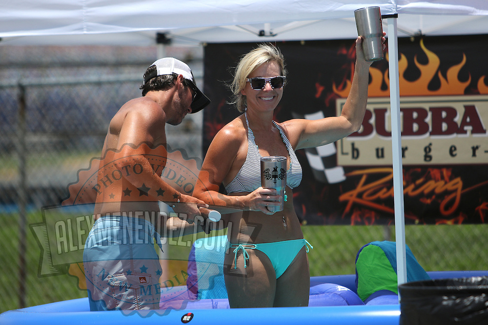 Spectators prepare for a swim with sunscreen in the infield camping area prior to the 57th Annual NASCAR Coke Zero 400 stock car race at Daytona International Speedway on Sunday, July 5, 2015 in Daytona Beach, Florida.  (AP Photo/Alex Menendez)