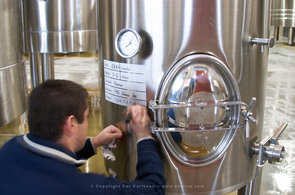 Winery worker marking in felt pen on a stainless steel tank. Bodega NQN Winery, Vinedos de la Patagonia, Neuquen, Patagonia, Argentina, South America