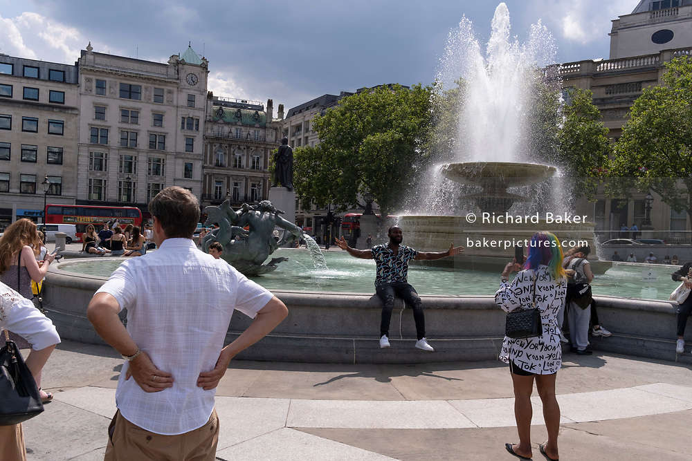 A man expresses joy at the fountains in Trafalgar Square on Covid 'Freedom Day'. This date is what Prime Minister Boris Johnson's UK government has set as the end of strict Covid pandemic social distancing conditions with the end of mandatory face coverings in shops and public transport, on 19th July 2021, in London, England.