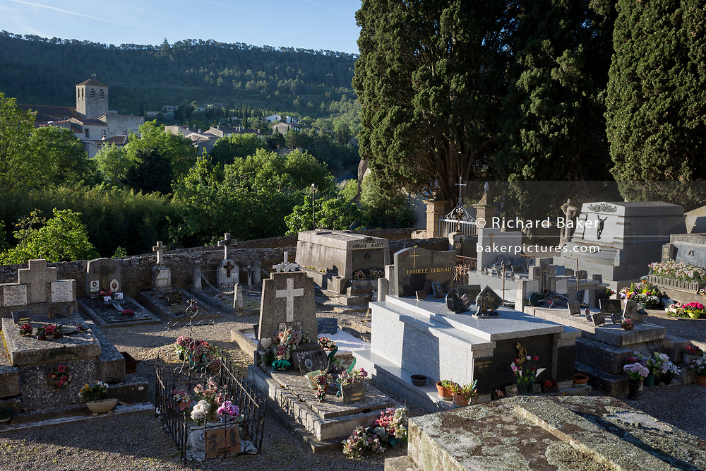 The village cemetery of Lagrasse and the church of Sant-Michel in the distance, on 21st May 2017, in Lagrasse, Languedoc-Rousillon, south of France. Lagrasse is listed as one of France's most beautiful villages and lies on the famous Route 20 wine route in the Basses-Corbieres region dating to the 13th century.