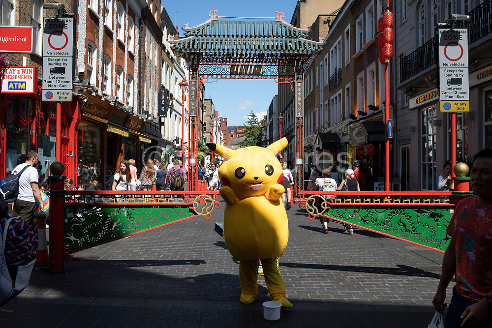 Pokemon Pikatchu who people pay to have their picture taken with at the end of Gerradr Street in Chinatown, London, England, United Kingdom. Pikachu are a species of Pokemon, fictional creatures that appear in an assortment of video games, animated television shows and movies, trading card games, and comic books licensed by The Pokémon Company, a Japanese corporation.