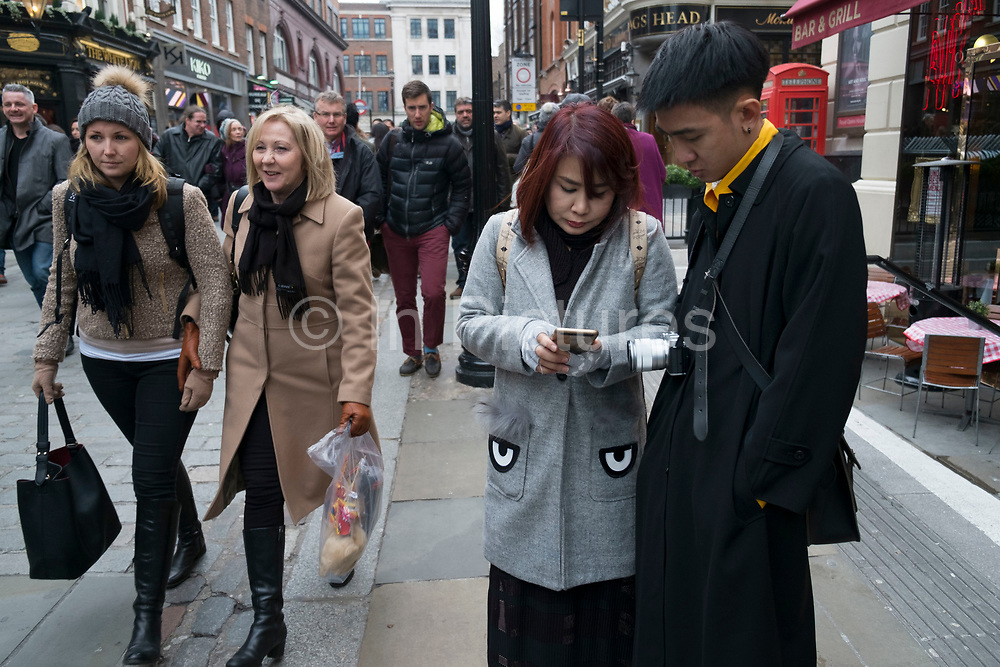 Chinese woman with eyes on her coat pockets texting on her phone during Chinese New Year celebrations in central London, United Kingdom. Tens of thousands of people gathered in the West End filling the streets and joining in with the festival atmosphere. (photo by Mike Kemp/In Pictures via Getty Images)