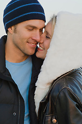 couple in winter clothes smiling and snuggling together