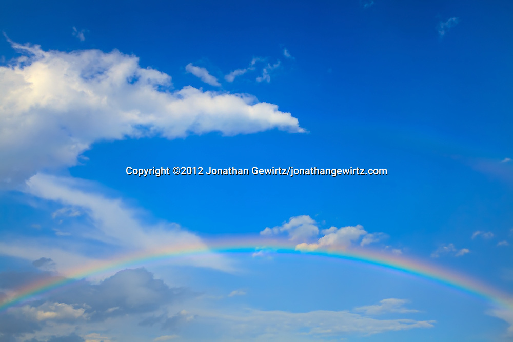 A classic rainbow appears against the backdrop of a partly cloudy blue sky. WATERMARKS WILL NOT APPEAR ON PRINTS OR LICENSED IMAGES.