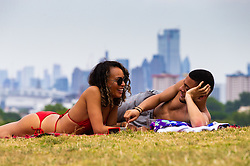 As clouds start building up over the city skyline, Laura Scougall, 30, and Max St Hill enjoy the hot weather where London temperatures are exceeding 37ºC on Primrose Hill. London, July 25 2019.
