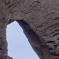 CHINA, Xinjiang. Climbers (MR) look up at huge Shipton's Arch, one of earth's biggest, in arid Kara Tagh Mountains near Kashgar.
