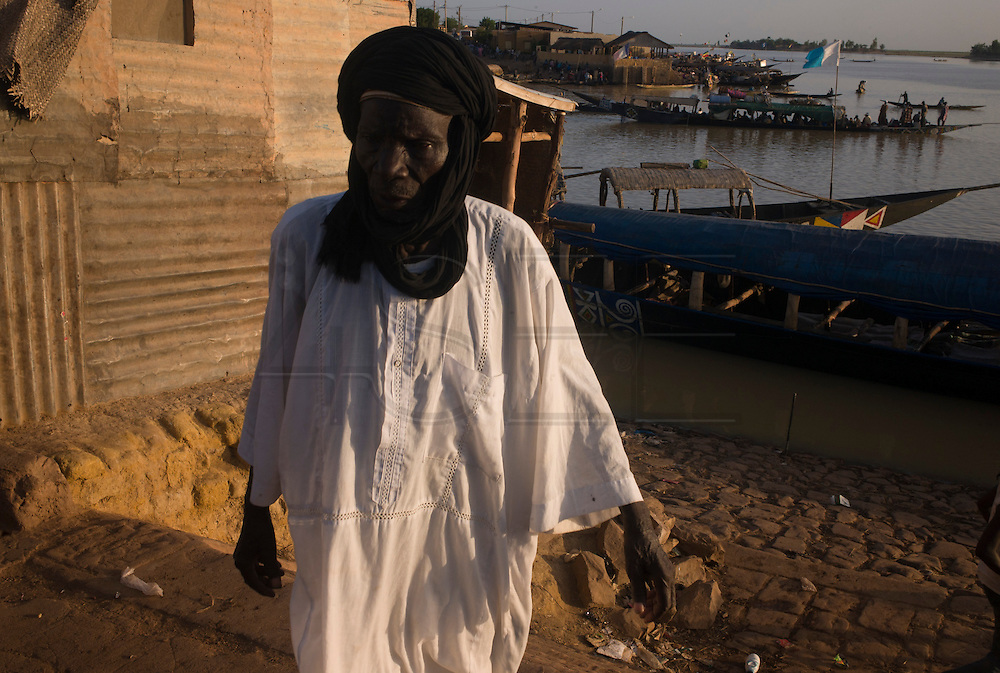 A man dressed with touareg clothes, unload a boat in Mopti's harbour. At the confluence of the Niger and the Bani rivers, between Timbuktu and Ségou, Mopti is the second largest city in Mali, and the hub for commerce and tourism in this west-african landlocked country.