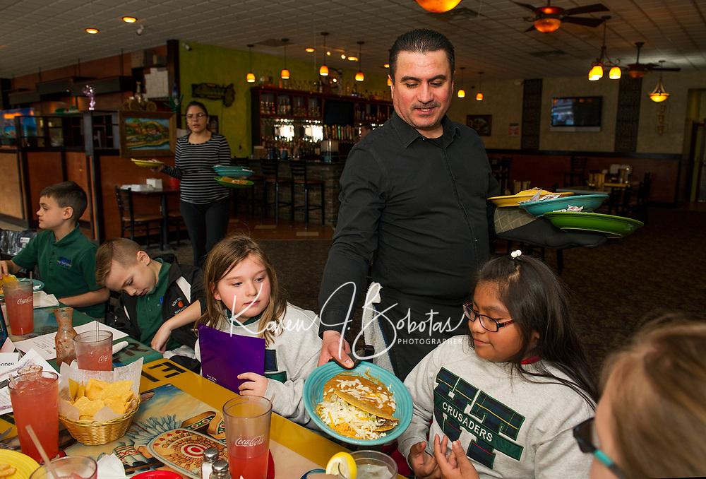 "Antonio Leon serves an order of ""Un taco de carne, arroz Esponol y frijoles fritos"" to Eli during Holy Trinity School's Spanish field trip to El Jimador in Belmont Thursday afternoon.  (Karen Bobotas/for the Laconia Daily Sun)"