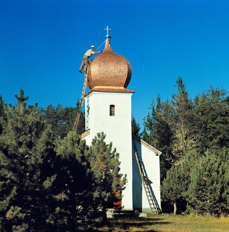 A man repairs the roof of a small church near San Carlos de Bariloche, Argentina.