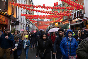 Rain for Chinese new year celebrations on Gerrard Street in Chinatown on 26th January 2020 in London, England, United Kingdom. Local Chinese community and Londoners gather on this famous area of central London which is the focus of celebrations for this, the Chinese Year of the Rat. Bright red lanterns are strung across between the buildings creating a canopy of colour.