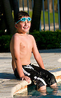 Portrait of a kid seating in a swimming pool.