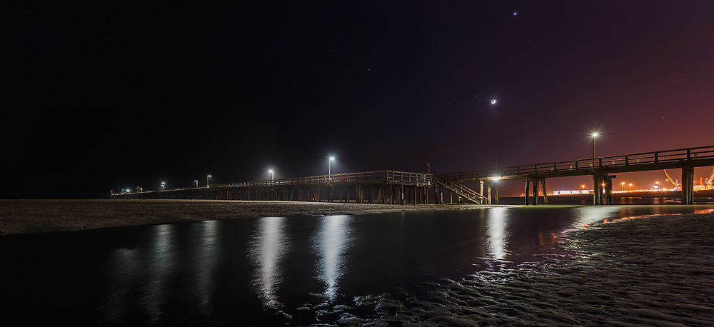 A crescent moon hangs in the night sky over Port Hueneme Beach as a river cuts across the sand.