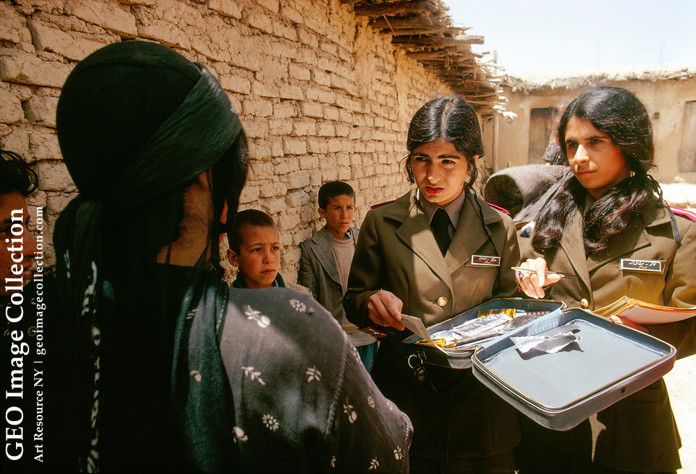 Women of the Revolution's Health Corps hand out pills and information.