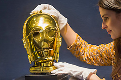 "© Licensed to London News Pictures. 06/12/2019. LONDON, UK. A staff member poses with a ""Return Of The Jedi Promotional C-3PO Helmet"", 1983 (Estimate GBP15,000-20,000), at the preview of ""Star Wars Online"", a sale dedicated to Star Wars collectibles encompassing 100 lots from the franchise.  Sotheby's will host the online-only sale which will run until 13 December, ahead of the final film in the sequel trilogy ""Star Wars: The Rise of Skywalker"".  Highlights from the sale are on display at Sotheby's New Bond Street 6 to 11 December  Photo credit: Stephen Chung/LNP"