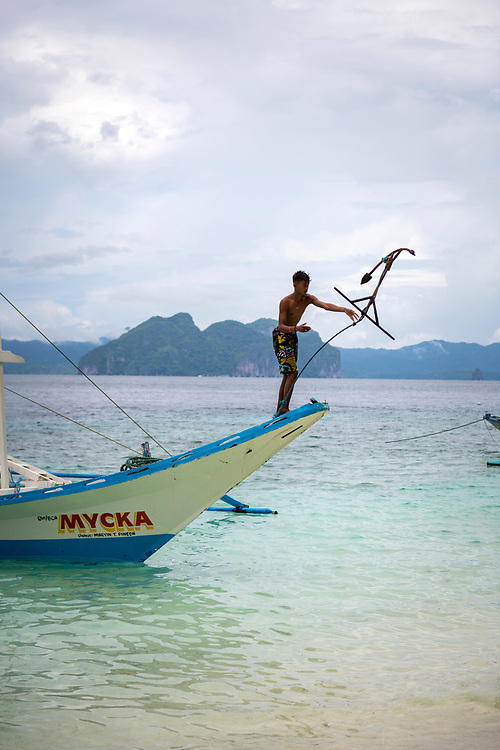 El Nido, Philippines - July 14, 2019: A crew member throws the anchor off a traditional bangka boat at Entalula Island, located in the Bacuit Archipelago near El Nido, Palawan; Philippines. The island is a popular stop on a day-long boat tours out of El Nido.