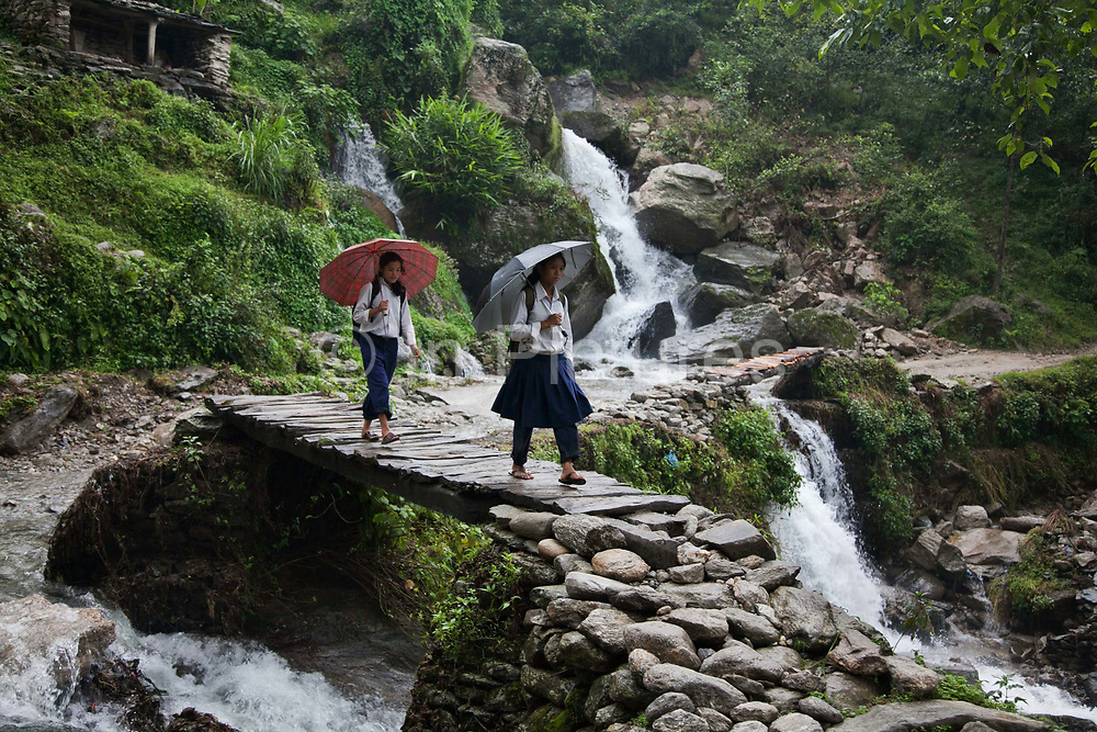 Two school girls are making their way home after school along a mountain road in Dolakha district. The summer months is the rainy season and rivers of rain water is gushing down the moutains and across the roads.