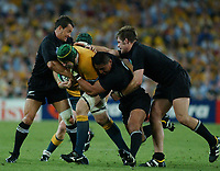 Photo: Steve Holland.<br />New Zealand v Australia. Semi-Final, at the Telstra Stadium, Sydney. RWC 2003. 15/11/2003. <br />David Lyons powers through the tackles from Carlos Spencer, Jerry Collins and Richie McCaw.