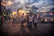 Carrying the God's palanquin down a major city road during an evening religious festival.