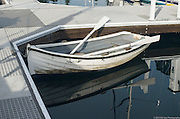 A white wooden dinghy rests on still morning water in the marina at Winslow, Washington