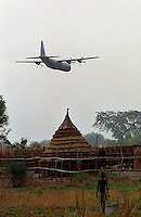 csz980429sudan1c:a c130 hercules flies over a village on its way to drop 16 tonnes of grain at a world vision food distributuion site, pre famine conditions in bahr el ghazal regeon of southern sudan threaten the lives of 500,000 people: pic craig sillitoe: story helen signy (smh): news extra melbourne photographers, commercial photographers, industrial photographers, corporate photographer, architectural photographers, This photograph can be used for non commercial uses with attribution. Credit: Craig Sillitoe Photography / http://www.csillitoe.com<br /> <br /> It is protected under the Creative Commons Attribution-NonCommercial-ShareAlike 4.0 International License. To view a copy of this license, visit http://creativecommons.org/licenses/by-nc-sa/4.0/.