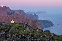 Midnight twilight of summer over wild camp on summit of Storskiva, Moskenesøy, Lofoten Islands, Norway