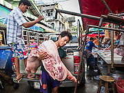 "12 JUNE 2015 - BANGKOK, THAILAND: Delivery of fresh pork in Khlong Toey Market in Bangkok. Khlong Toey (also called Khlong Toei) Market is one of the largest ""wet markets"" in Thailand. The market is located in the midst of one of Bangkok's largest slum areas and close to the city's original deep water port. Thousands of people live in the neighboring slum area. Thousands more shop in the sprawling market for fresh fruits and vegetables as well meat, fish and poultry.          PHOTO BY JACK KURTZ"