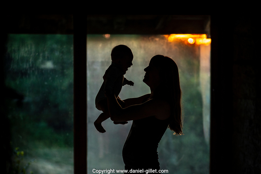 Silhouette of a Young Mother holding her daughter in her arms at dusk