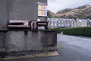 Armchair soft furniture has been left outside flats, on 3rd October 2021, in Blaenau Ffestiniog, Gwynedd, Wales.