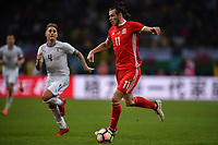 """Gareth Bale of Wales national football team dribbles against Uruguay national football team in their final match during the 2018 Gree China Cup International Football Championship in Nanning city, south China's Guangxi Zhuang Autonomous Region, 26 March 2018.<br /> <br /> Edinson Cavani's goal in the second half helped Uruguay beat Wales to claim the title of the second edition of China Cup International Football Championship here on Monday (26 March 2018). """"It was a tough match. I'm very satisfied with the result and I think that we can even get better if we didn't suffer from jet lag or injuries. I think the result was very satisfactory,"""" said Uruguay coach Oscar Tabarez. Wales were buoyed by a 6-0 victory over China while Uruguay were fresh from a 2-0 win over the Czech Republic. Uruguay almost took a dream start just 3 minutes into the game as Luis Suarez's shot on Nahitan Nandez cross smacked the upright. Uruguay were dealt a blow on 8 minutes when Jose Gimenez was injured in a challenge and was replaced by Sebastian Coates. Inter Milan's midfielder Matias Vecino of Uruguay also fired at the edge of box from a looped pass but only saw his attempt whistle past the post. Suarez squandered a golden opportunity on 32 minutes when Ashley Williams's wayward backpass sent him clear, but the Barca hitman rattled the woodwork again with goalkeeper Wayne Hennessey well beaten."""