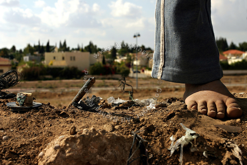 A child is standing barefoot in the unrecognised Bedouin village of Tarrabin el Sana, close to BeerSheva, the capital of the Negev, a large deserted area in the south of Israel. The village, bordering the wealthy Israeli settlement of Omer (visible in the background), is surrounded by barbed wire and bound to be demolished as it is deemed illegal by the authorities, willing to further expand Omer's borders. Numbering around 200.000 in Israel, the Bedouins constitute the native ethnic group of these areas, they farm, grow wheat, olives and live in complete self sufficiency. Many of them were in these lands long before the Israeli State was created and their traditional lifestyle is now threatened by subtle Governmental policies. The seven Bedouin towns already built are all between the 10 more impoverished towns in Israel.