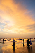 Groups of people stand at the shoreline to admire the dramatic sky at sunset on Laboni Beach, Cox Bazar, Chittagong Division, Bangladesh, Asia. The wispy clouds are glowing orange from the sun set.