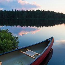 A canoe on Little Berry Pond in Maine's Northern Forest. Sunset. Cold Stream watershed, Johnson Mountain Township.