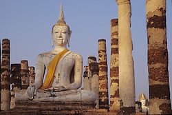 Asia, Thailand, Sukhothai. Buddha and stone pillars in ruins of Wat Mahathat in Old Sukhothai (13th c.) Thailand's first capital