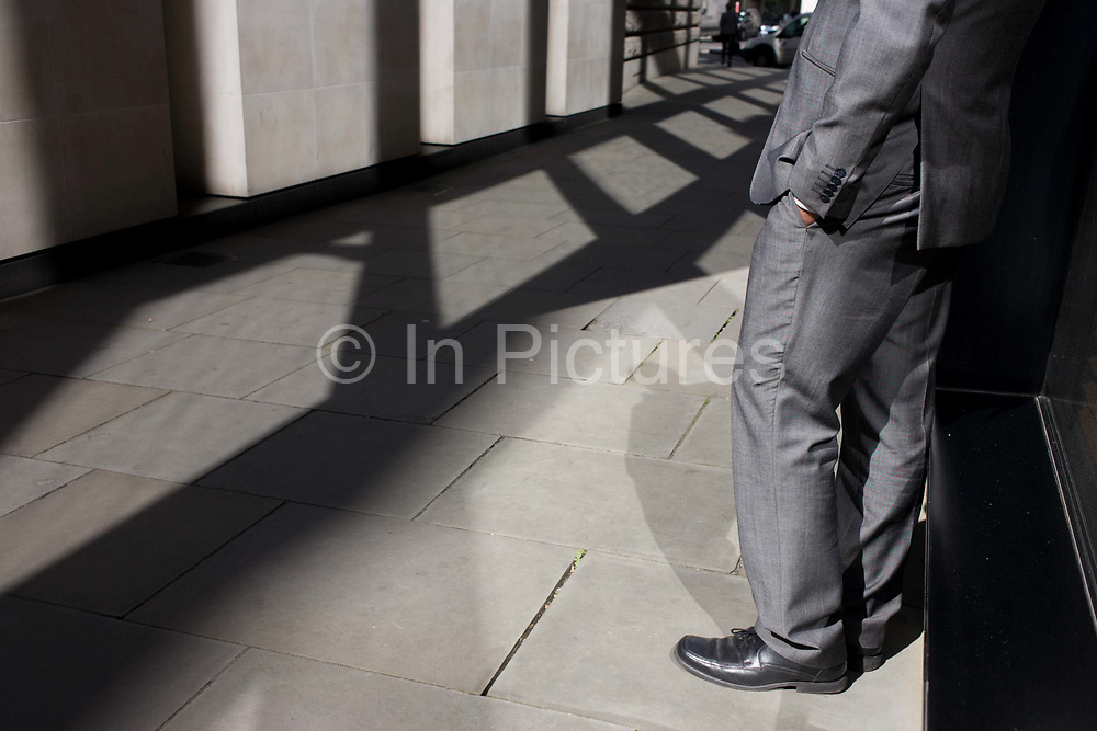 An anonymous man wearing shiny grey suit and polished black shoes stands in narrow sunlit lane in the City of London. With a hand in a pocket, the anonymous man smokes a cigarette during a break in his working day. It is mid-afternoon and the male enjoys warm spring sunshine in this narrow pedestrian lane He is a grey man in grey clothing, suitably merging with monochrome architecture and landscape.