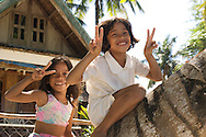 Two Filippino children play on a palm tree on the beach in El Nido Town, the Philippines.