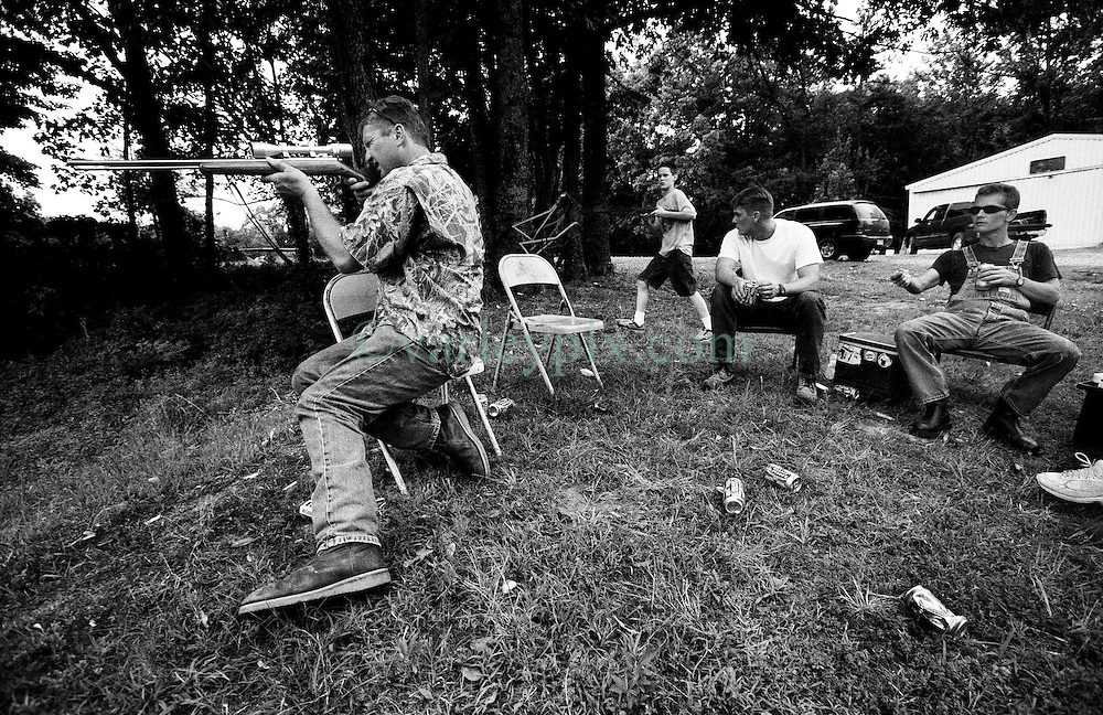June 15th, 2003. Wynne, Arkansas. .Guns in America. Shooting snakes on a lake. Drinking, smoking and shooting. A family scene from the backwoods of Arkansas near the town of Wynne..Photo; Charlie Varley