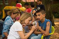 DEU, Deutschland, Germany, Berlin, 19.08.2015: Freiwillige Helfer der Initiative Moabit Hilft bemalen Flüchtlingskinder auf dem Gelände des Landesamts für Gesundheit und Soziales (LaGeSo), hier befindet sich die Zentrale Aufnahmeeinrichtung des Landes Berlin für Asylbewerber.