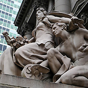 The Four Continents sculpture by Daniel Chester French in front of the  George Gustav Heye Center of the Smithsonian Institute's National Museum of the American Indian and across the street from the 2 Broadway building in New York, New York, USA.  The America sculpture is pictured, one of four in the series.