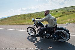 Jeff Hampton of Colorado Springs, CO riding his Harley-Davidson south on highway 79 toward Sturgis during the annual Sturgis Black Hills Motorcycle Rally. SD, USA. August 3, 2014.  Photography ©2014 Michael Lichter.