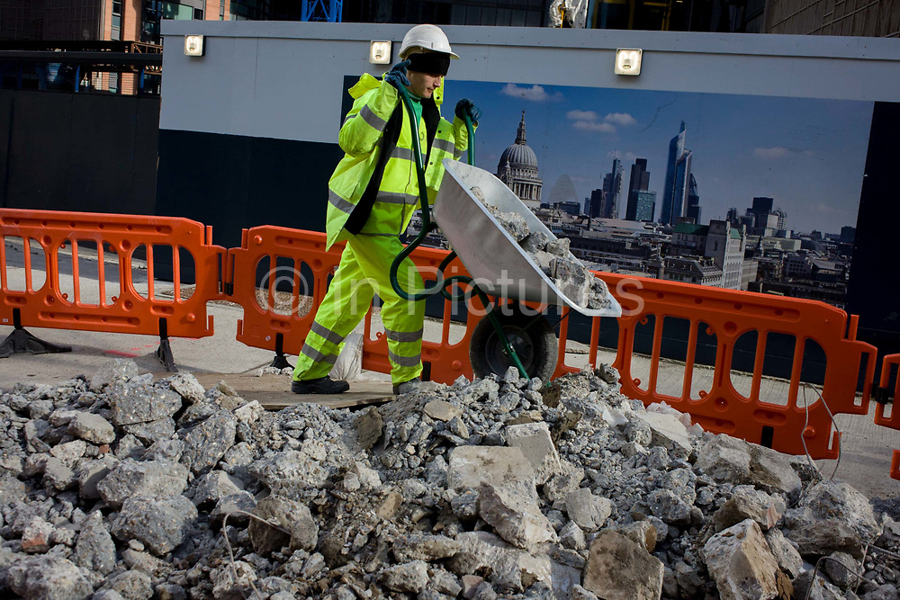 A workman tips broken up concrete on to a growing pile of construction rubble near an skyline illustration of the City of London. Illuminated by sunshine and its reflections from nearby sheet glass windows, the young man tilts the barrow so that the concrete is added to the already large pile, fenced off in this City of London street, the heart of the capital's financial district. The Cityscape in the background tells us about the UK's capital including the towering dome of St Paul's Cathedral and other financial institutions.