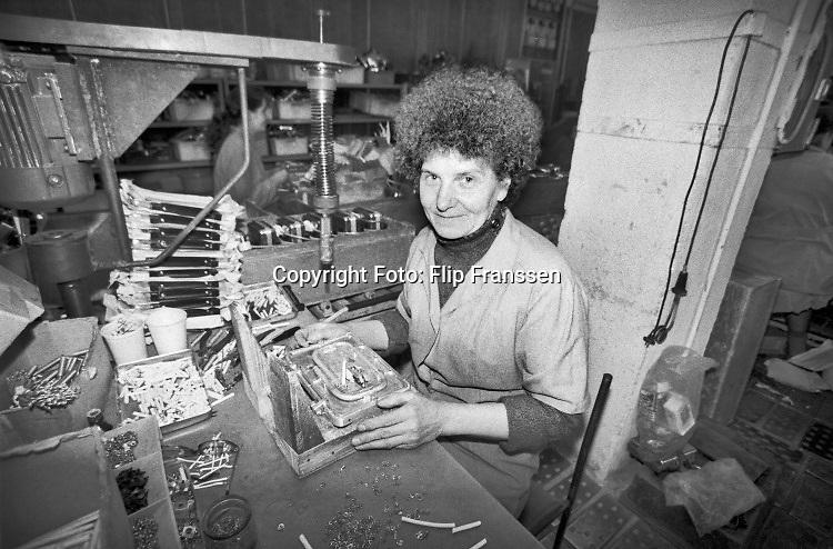 Rusland, Pskov, 5-5-1991Serie, reportage, uit een russische fabriek waar in de overgangsperiode tussen het communisme en de vrije markt economie vooral door vrouwen kleine huishoudelijke apparaten gemaakt worden. Metaalfabriek. De arbeidsomstandigheden zijn slecht en ongezond .Foto: Flip Franssen