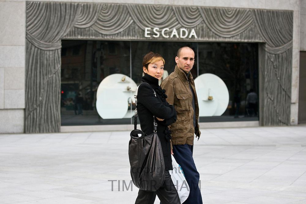 Couple walk past Escada shop on Nanjing Road, central Shanghai, China