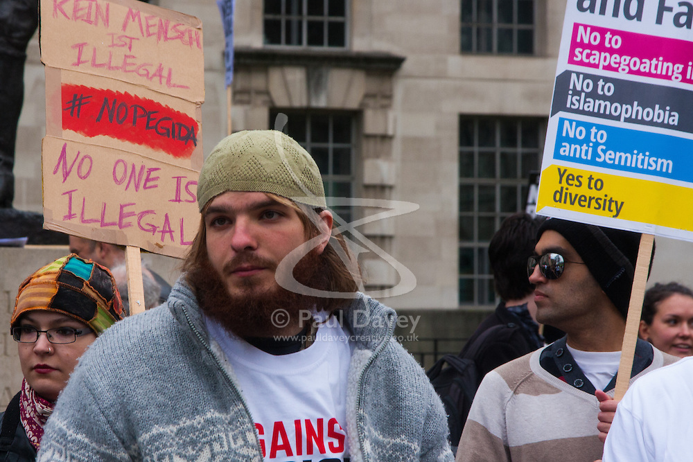 Whitehall, London, April 4th 2015. As PEGIDA UK holds a poorly attended rally on Whitehall, scores of police are called in to contain counter protesters from various London anti-fascist movements. PICTURED: Anti-racism campaigners were there in their scores to counter the PEGIDA rally.