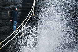 © London News Pictures. 22/02/2017. Aberystwyth, UK.<br /> A young man risks life and limb by standing on the steps of the promenade as storm waves from the leading edge of Storm Doris  break around him. Conditions have been wet, misty and windy in Aberystwyth on the west Wales coast, as the weather begins to deteriorate in advance of Storm Doris, the fourth named storm of the winter, hitting the UK tomorrow (Thurs). Photo credit: Keith Morris/LNP