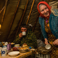 North of the Arctic Circle in Russia, 77-year old Marie Terentéva, a matriarch of the last nomadic Komi reindeer herding clan, serves dinner to her son Vasily  in the family's chum (tepee).