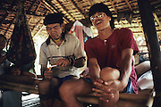 NOMADIC PENAN, MALAYSIA. Sarawak, Borneo, South East Asia. Old man and youth, tradition and modern. Cigarette smoking. Tropical rainforest and one of the world's richest, oldest eco-systems, flora and fauna, under threat from development, logging and deforestation. Home to indigenous Dayak native tribal peoples, farming by slash and burn cultivation, fishing and hunting wild boar. Home to the Penan, traditional nomadic hunter-gatherers, of whom only one thousand survive, eating roots, and hunting wild animals with blowpipes. Animists, Christians, they still practice traditional medicine from herbs and plants. Native people have mounted protests and blockades against logging concessions, many have been arrested and imprisoned.