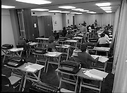 Conference Room at the EEC Building.   (N60)..1981..07.02.1981..02.07.1981..7th February 1981...At the EEC offices, 39 Molesworth Street, the conference room was converted to an examination hall for the purpose of recruiting staff..Image shows the room laid out with secretarial equipment as the applicants take their places for the exam.The invigilator hands a note pad to a candidate.
