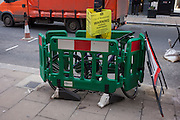 A bike has been fenced in between some construction barriers and beneath a parking suspension warning sign in Bond Street, on 15th December 2016, in London, England.